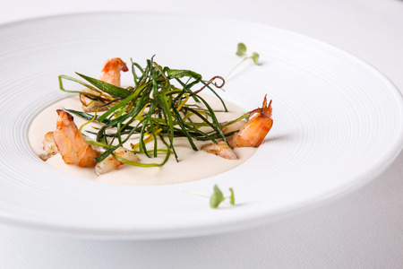 Cream soup with shrimps in a white round plate on a white background