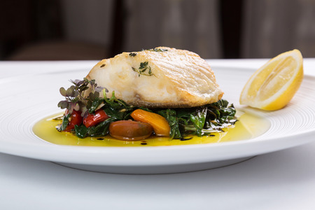 barramundi: Fish filet served with grilled vegetables on a white plate