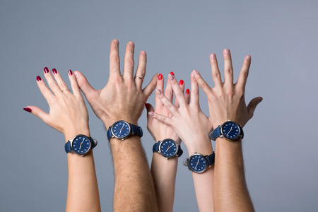 Raised up human hands in a   spontaneous movement  of unity wearing identical watches