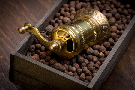 Metal pepper mill in eastern style lying in a wooden box filled with sweet-scented pepper Stock Photo