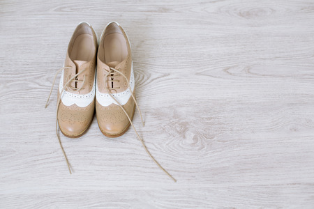 business shoes: Pair of new unlaced womans shoes on a white wooden floor