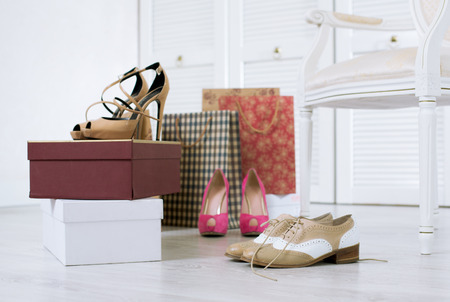 Three pairs of just purchased and unboxed shoes on a floor of a wardrobe