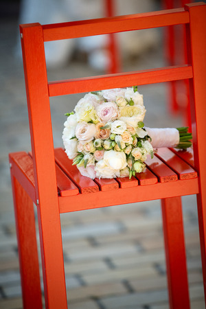 Wedding bouquet lying on a red chair on a location Stock Photo