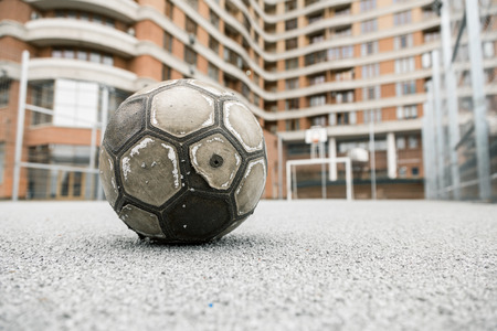 Old worn leather ball  on a playground