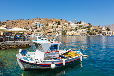 tripping: SYMI, GREECE - September 6,2015: Fishing boats moored in Yialos harbour and a beautiful view on a color houses on Symi island, Greece. Symi is easy and most popular destination for day tripping from Rhodes island.