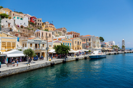 tripping: SYMI, GREECE - JUNE 12, 2015: The main street along the coast in Yialos harbour on June 12, 2015 on Symi island, Greece. Symi is easy and most popular destination for day tripping from Rhodes island. Editorial