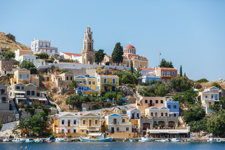 tripping: SYMI, GREECE - JUNE 12,2015: View of a coastline street and fishing boats moored in Yialos harbour on June 12, 2015 on Symi island, Greece. Symi is easy and most popular destination for day tripping from Rhodes island.