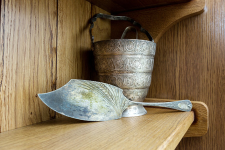 shelf ice: Vintage silver paddle and ice bucket with tongs standing on an oak shelf