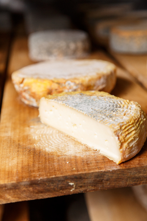 Pie?e of young and soft goat cheese head with a blue mold on a wooden shelf in a cellar on a private farm. Cheese manufacture Stock Photo