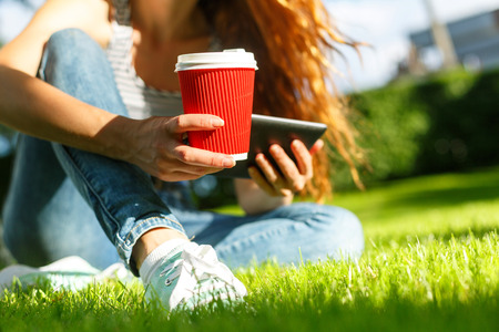 Young woman with red disposable paper cup of coffee using tablet pc on a green lawn in a park