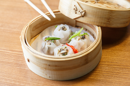 sums: Dim sums with pork and mushrooms in a bamboo steamer on a wooden table in asian restaurant
