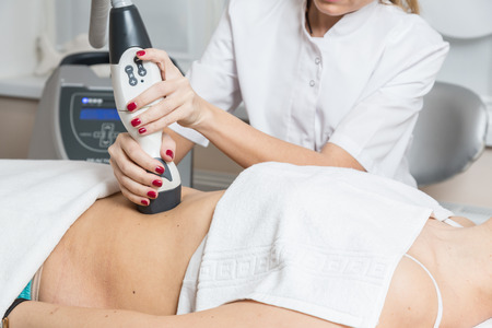 Cosmetician  making procedure of lymphatic drainage with a professional equipment Stock Photo