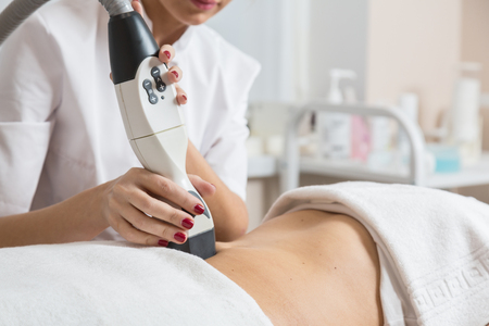 Cosmetician  making procedure of lymphatic drainage with a professional equipment 스톡 콘텐츠