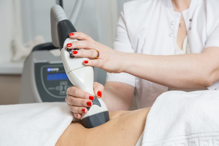 lymphatic drainage therapy: Cosmetician  making procedure of lymphatic drainage with a professional equipment Stock Photo