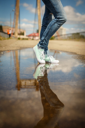 foots: Woman in sport shoes standing in a puddle. Close up shot of foots in a water