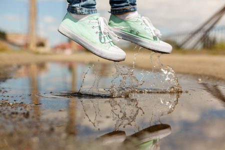foots: Foots of a woman in a sport shoes flying over a puddle diring jumping. Close up shot of foots over the water
