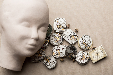 time flies: Human head made of clay lying over clock mechanisms and dials.  time goes by, running out of time,  time flies .