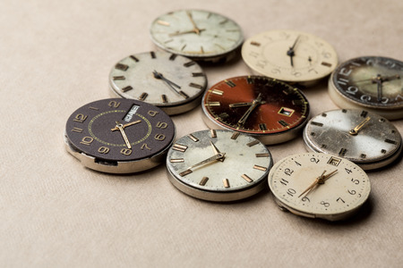 Wrist watch dials lying on a neutral background