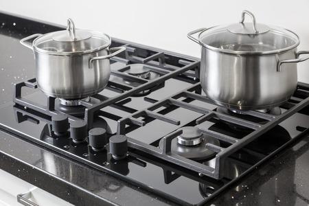 New iron pots on a black gas stove on a kitchen Stock Photo