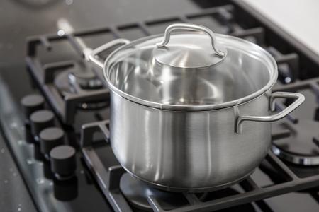 New iron pot on a black gas stove on a kitchen Stock Photo