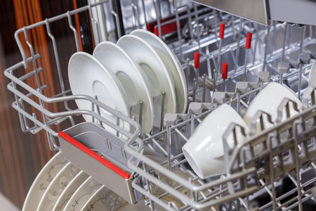 Clean dishes in open dishwasher machine