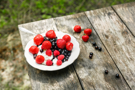 Cottage cheese with summer berries - strawberry, raspberry and black currant in a white plate on a worn wooden background. Open air healthy meal