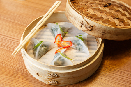 Dim sums with spinach and tofu cheese  in a bamboo steamer on wooden table in asian restaurant