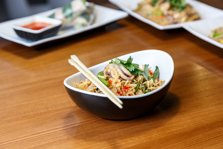 Asian rise with seafood and vegetables in oval plate with bamboo sticks on a wooden table in asian restaurant