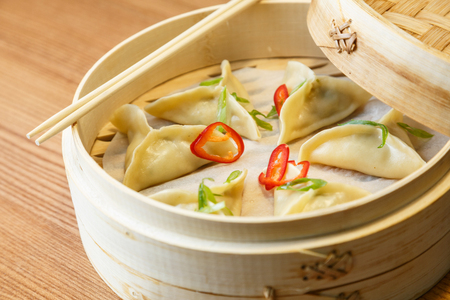 sums: Dim sums - wontons -with a chicken meat  in a bamboo box on wooden table in asian restaurant Stock Photo