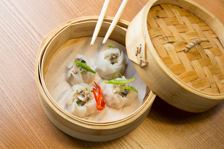 Dim sums with pork and mushrooms in a bamboo steamer on a wooden table in asian restaurant
