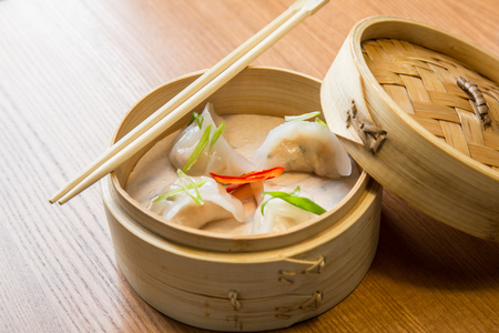 Dim sums with shrimps in a bamboo steamer on a wooden table in asian restaurant