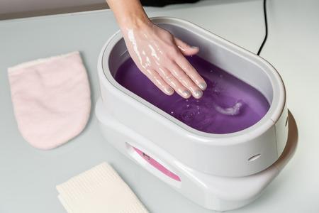 Manos femeninas que toman procedimiento en un recipiente de cera de parafina de color lila. equipo cosmético y de cuidado de la piel en un salón de belleza y spa.