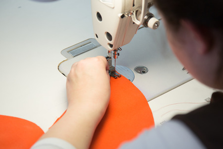 Sewing Process - womans hands using sewing machine on a sewing manufacture Stock Photo