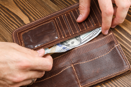 man is putting 100 dollar banknote in a brown leather wallet over dark wooden background. Close up shot of hands and wallet Stock Photo