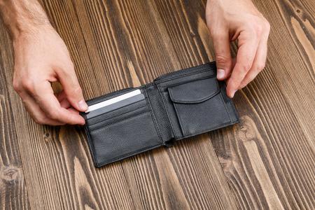 Black mans wallet in man hands over dark wooden background Stock Photo