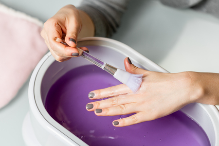 Female hands taking procedure in a lilac paraffin wax  bowl. Cosmetological and skincare equipment in a beauty & spa salon.