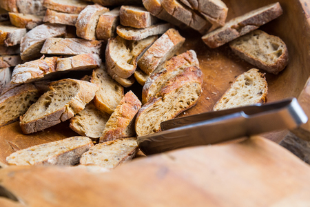 tongs: Slices of brown bread in a wooden bowl with iron tongs