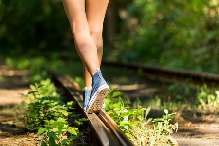 Young woman with beautiful sporty legs walking on rails in jeans sneakers