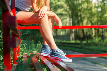 Young woman with beautiful sporty legs sitting on a red bus stop in jeans sneakers