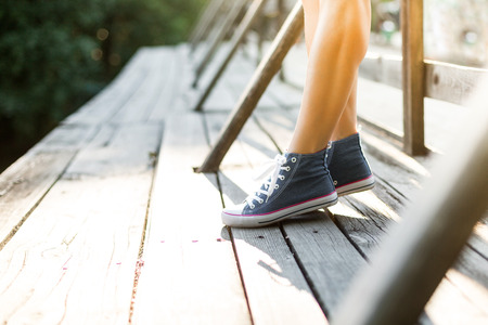 Young woman with beautiful sporty legs standing on a wooden bridge railing in jeans sneakers
