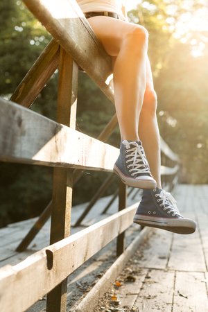Young woman with beautiful sporty legs sitting on a wooden bridge railing in jeans sneakers