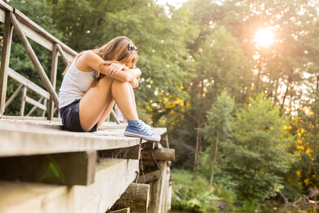 Young sad woman with beautiful sporty legs sitting on a wooden bridge railing in jeans sneakers