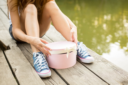 Young woman with beautiful sporty legs in jeans sneakers  sitting on a wood  opening pink gift box