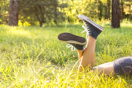 Woman legs wearing jeans sneakers lying on a grass in a forest lawn in the evening