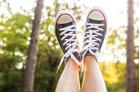 Close view of woman legs  wearing jeans sneakers over a sunset reys in a forest