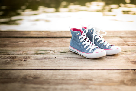 pair of jeans sneakers standinf on a wooden pier over the water background