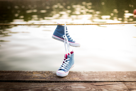 Tied pair of jeans sneakers hanging on a railings over the water background