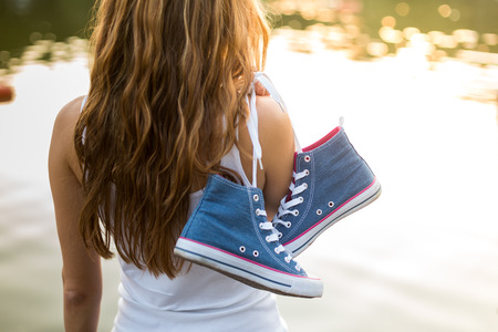 Outdoor lifestyle close-up  view of of tied pair of jeans sneakers hanging  on a finger of a  beautiful young woman over the shoulder . Stock Photo