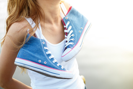 Outdoor lifestyle close-up  view of tied pair of jeans sneakers hanging  on the neck of a  beautiful young woman