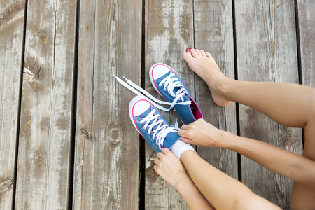 Outdoor lifestyle close-up of the legs of beautiful young woman girl. Young woman tying laces of her jeans sneakers sitting on the wooden floor